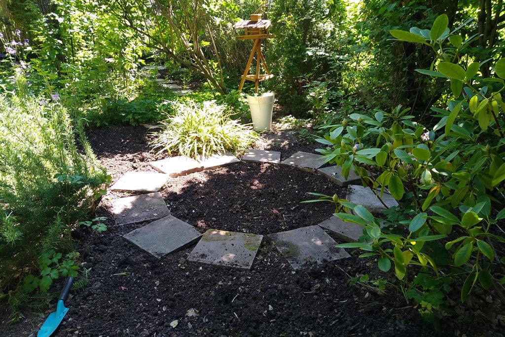 Kreis aus Gehwegplatten im Gartenbeet